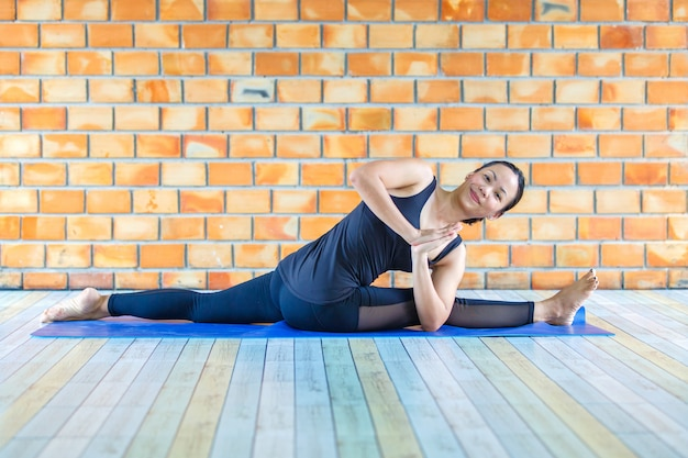 Estagiário asiático forte mulher praticando difícil yoga pose