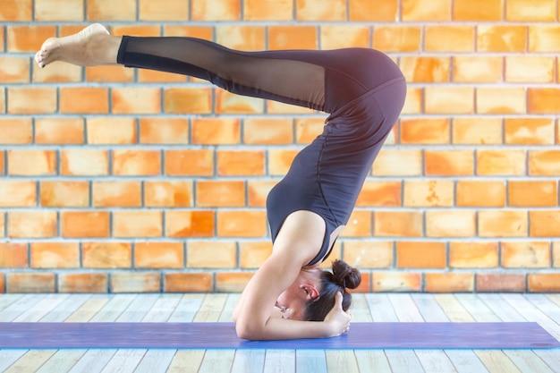 Estagiário asiático forte mulher praticando ioga difícil rajakapotasana rei pombo pose
