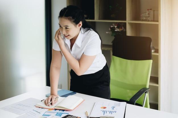 Estagiário de secretária fêmea jovem segurando o telefone para o programa de reunião de contato do cliente