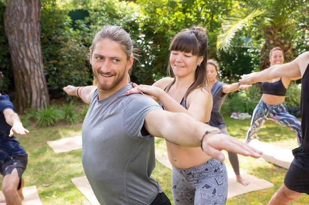 Estagiário de yoga positivo ajudando trainee