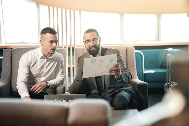 Estagiário próximo. investidor barbudo usando óculos e traje cinza escuro sentado perto de seu jovem estagiário