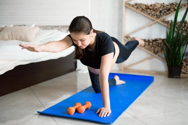 Estágio da gravidez. bela mulher grávida posando e tentando ioga.