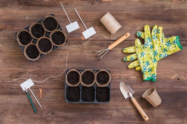 Estágios de plantio de sementes, vasos orgânicos com solo, ferramentas jardineiras e utensílios