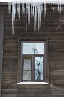 Estalactite de gelo pendurada no telhado com parede de madeira. insuficiente isolamento térmico do telhado. inverno