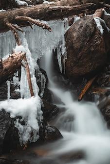 Estalactites de gelo em troncos em uma cachoeira