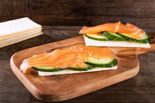 Estaladiço sem glúten, fatias de pepino e salmão defumado