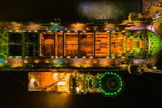 Estaleiro da indústria e reparação de grandes navios na vista aérea do mar à noite