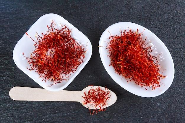Estames de especiarias de açafrão seco em uma placa branca em um quadro negro. fios vermelhos de açafrão.
