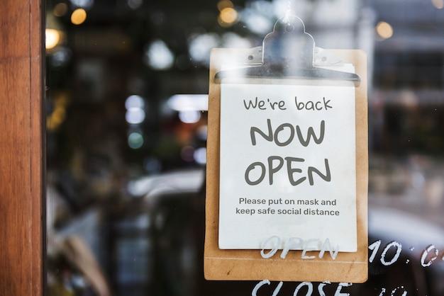 'estamos de volta, agora abertos' placa de café após a pandemia covid-19 Foto gratuita