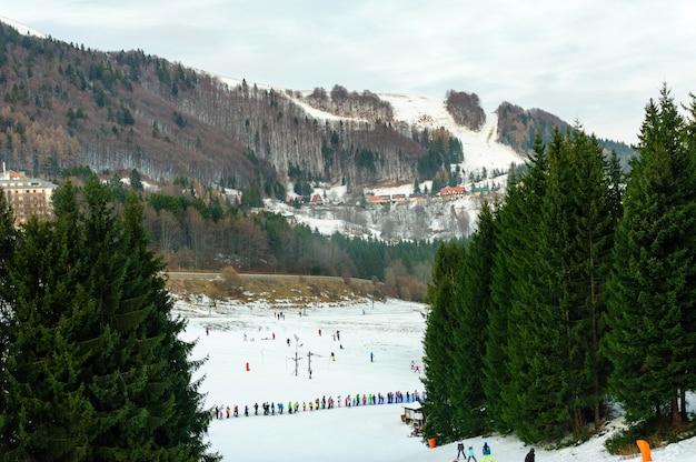 Estância de esqui em um belo dia de inverno; esquiadores e praticantes de snowboard esquiando ladeira abaixo até a base de um teleférico; árvores e montanhas