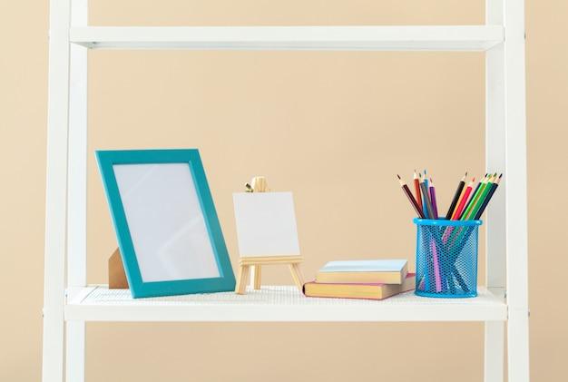 Estante branca com livros e artigos de papelaria contra a parede bege