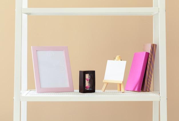 Estante branca com livros e artigos de papelaria contra parede bege