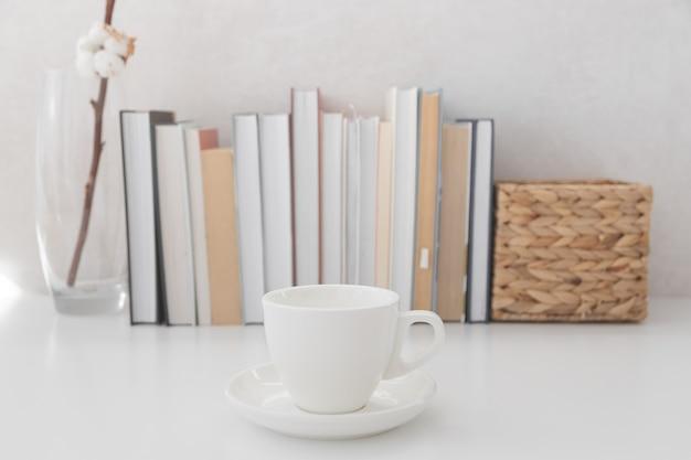 Estante com livros e copo de bebida quente em foco.