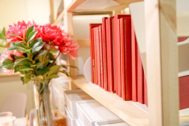 Estante de livros, livro vermelho na prateleira, conceito de educação
