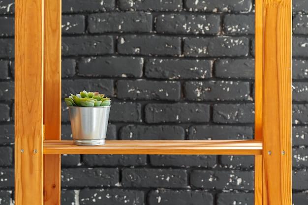Estante de madeira com livros e outras coisas contra a parede de tijolos pretos