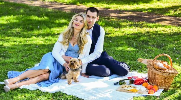 Estar apaixonado. lazer ao ar livre de verão. hora de relaxar. casal apaixonado. celebrando noivado. família no parque. comida e bebida. homem e mulher com cachorro. casal romântico no piquenique. encontro de amor na primavera.