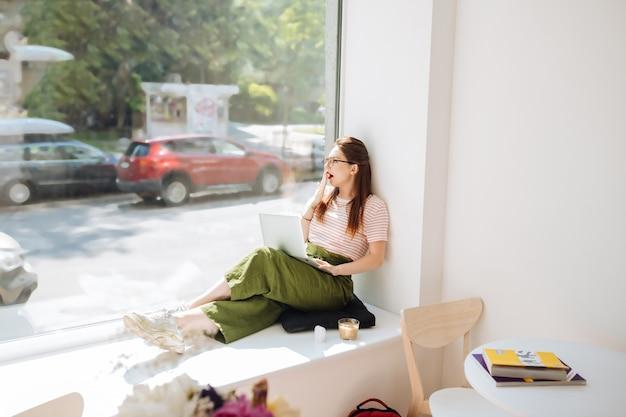 Estar cansado. linda garota segurando o laptop sobre os joelhos e olhando para a janela