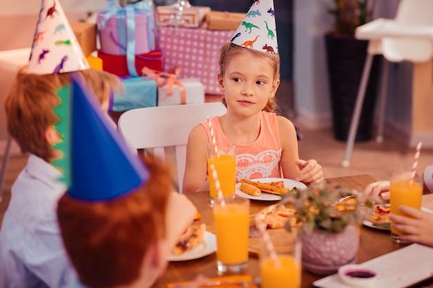 Estar em todos os ouvidos. loira linda sentada à mesa indo comer pizza