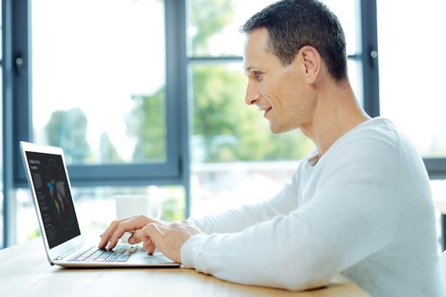 Estar focado. homem alegre positivo e encantado sentado em frente ao laptop e trabalhando nele enquanto se concentra em sua tarefa