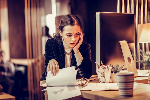 Estar ocupado. garota atenciosa franzindo a testa enquanto verifica os documentos