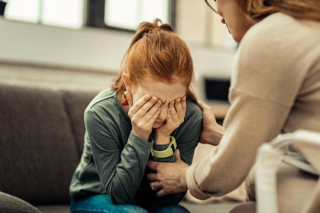 Estar triste. linda garota desanimada sentada no sofá pensando em seus problemas