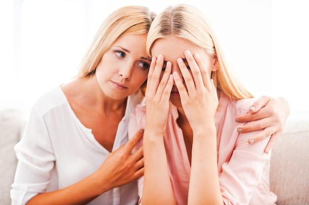 Estarei sempre com você em qualquer situação! linda mulher madura consolando sua filha chorando enquanto está sentada no sofá