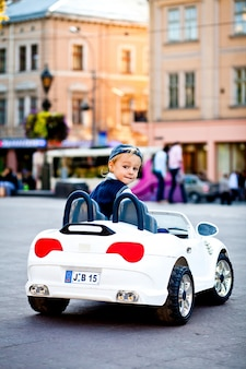 Estás bem? o menino encantador conduz o cabrio pequeno branco de bmw