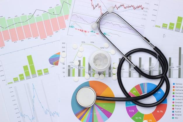 Estatísticas e análises médicas. estetoscópio e comprimidos de garrafa com gráficos e tabelas.