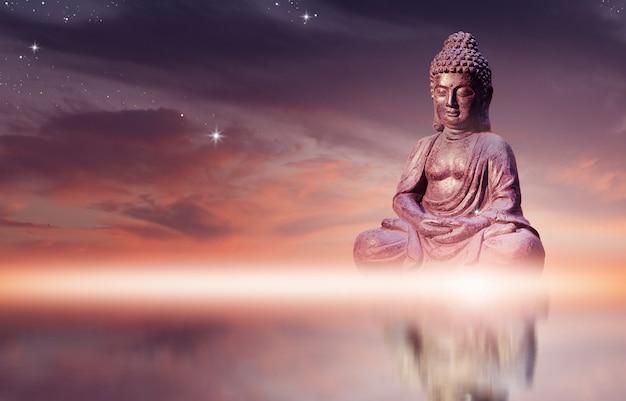 Estátua da buda que senta-se na pose da meditação contra o céu do por do sol com as nuvens douradas dos tons.