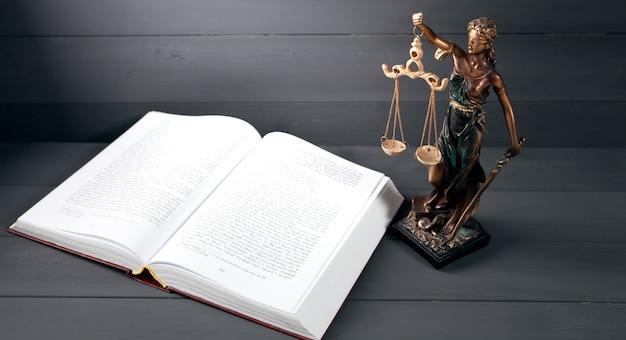 Estátua da justiça e livro sobre fundo cinza