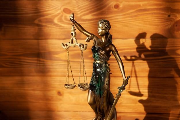 Estátua da justiça em fundo de madeira