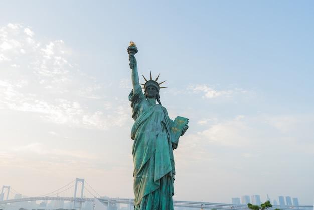 Estátua da liberdade em cidade com céu azul