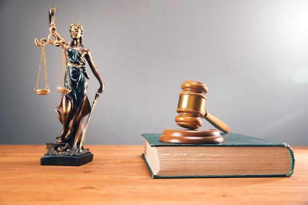 Estátua da senhora da justiça e o martelo do juiz no livro