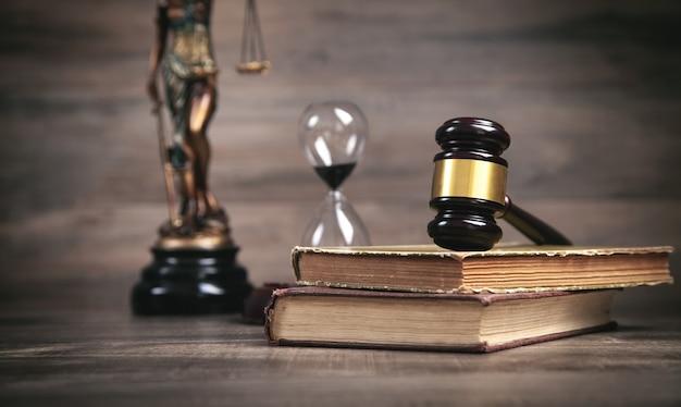 Estátua da senhora justiça, ampulheta, livro e martelo.