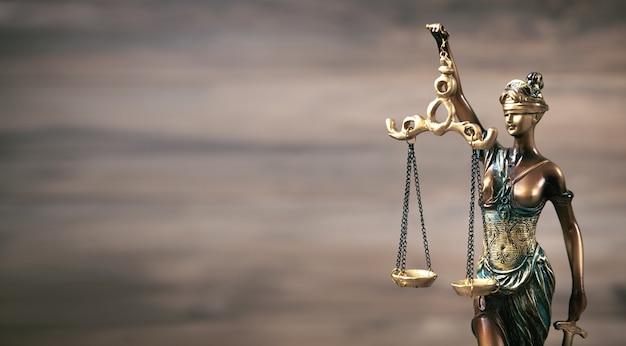Estátua da senhora justiça em fundo de madeira.
