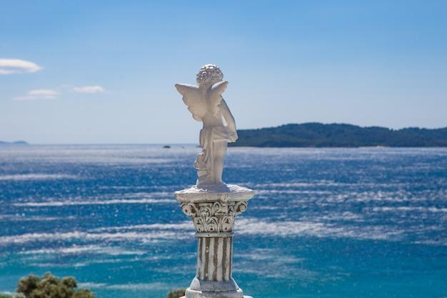Estátua de anjo branco fotografada por trás com um mar turvo
