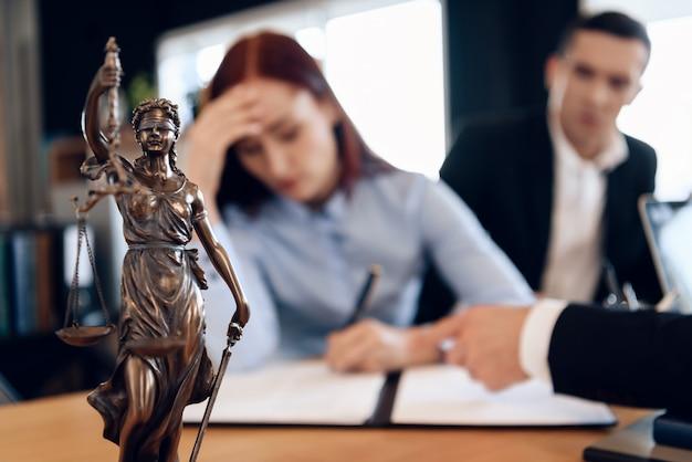 Estátua de bronze de themis detém escalas da justiça.