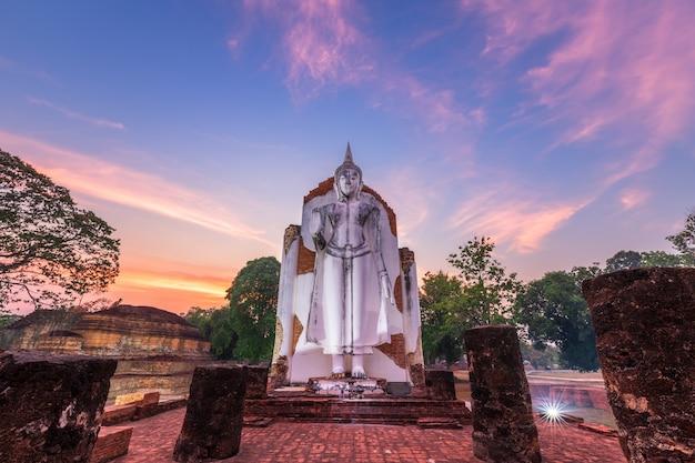 Estátua de buda branca antiga bonita ao pôr do sol é um templo budista