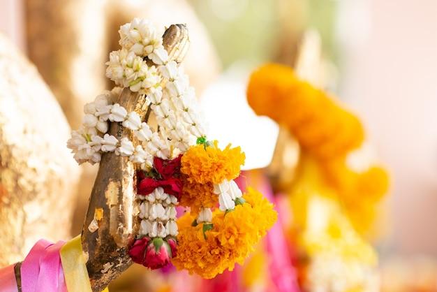 Estátua de buda com cru de latão. mão da estátua de buda com. guirlanda de calêndula e guirlanda de rosa. acredite, cultura, tradicional. os budistas acreditam e merecem. conceito de calma e meditação.