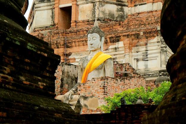 Estátua de buda com manto amarelo no templo antigo de wat yai chai mongkhon na cidade velha de ayutthaya, tailândia