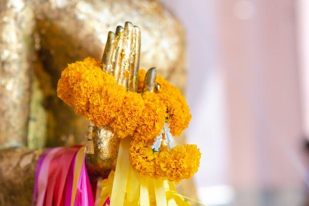 Estátua de buda com mão de bronze crua estátua de buda com guirlanda de calêndula e guirlanda de rosa. cultura de crença budista tradicional acredita e merece calma e conceito de meditação