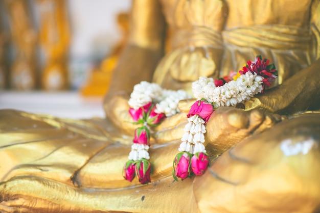 Estátua de buda com mão de bronze em bruto da meditação da estátua de buda com guirlanda de rosa no colo de buda