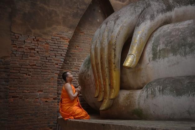 Estátua de buda e monges, wat si chum (templo) no parque histórico de sukhothai, sukhothai, tailândia,