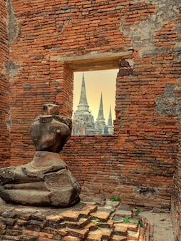 Estátua de buda quebrada perto da parede de tijolos com vista de três pagodes ou chedis antigos atrás do templo wat phra si sanphet na cidade histórica de ayutthaya, tailândia