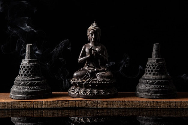 Estátua de buda sentado em meditação, com sinos budistas e fumaça de incenso