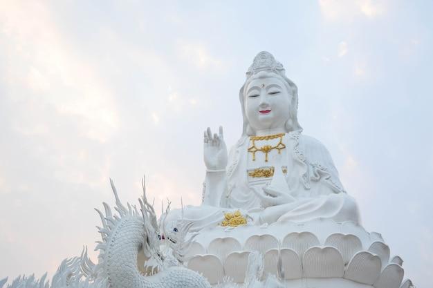 Estátua de dragão branco subindo para a grande estátua de guan yin em wat huay pla kang chiang rai