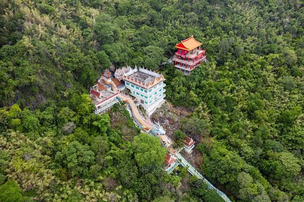 Estátua de dragão com templo e santuário vermelho na colina na floresta tropical em wat ban tham