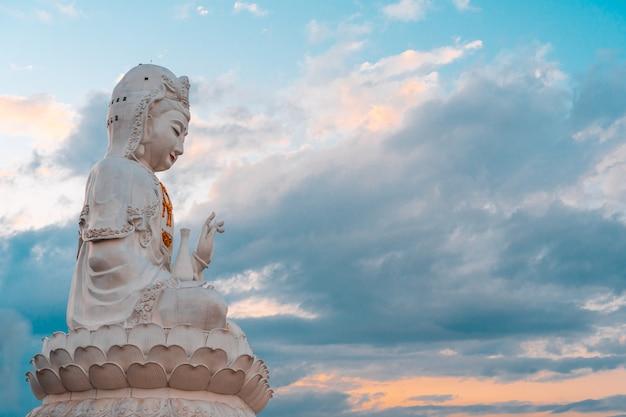 Estátua de guan yin com fundo natural do céu.