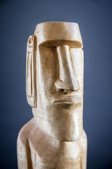 Estátua de madeira tradicional de uma moai da ilha de páscoa. fundo escuro
