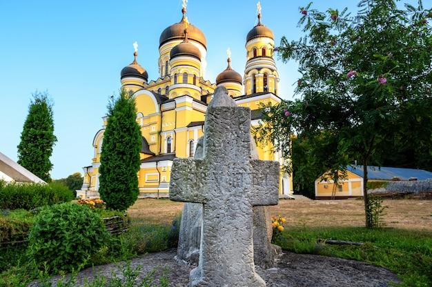 Estátua de pedra de uma cruz em frente ao mosteiro e a igreja de hancu.